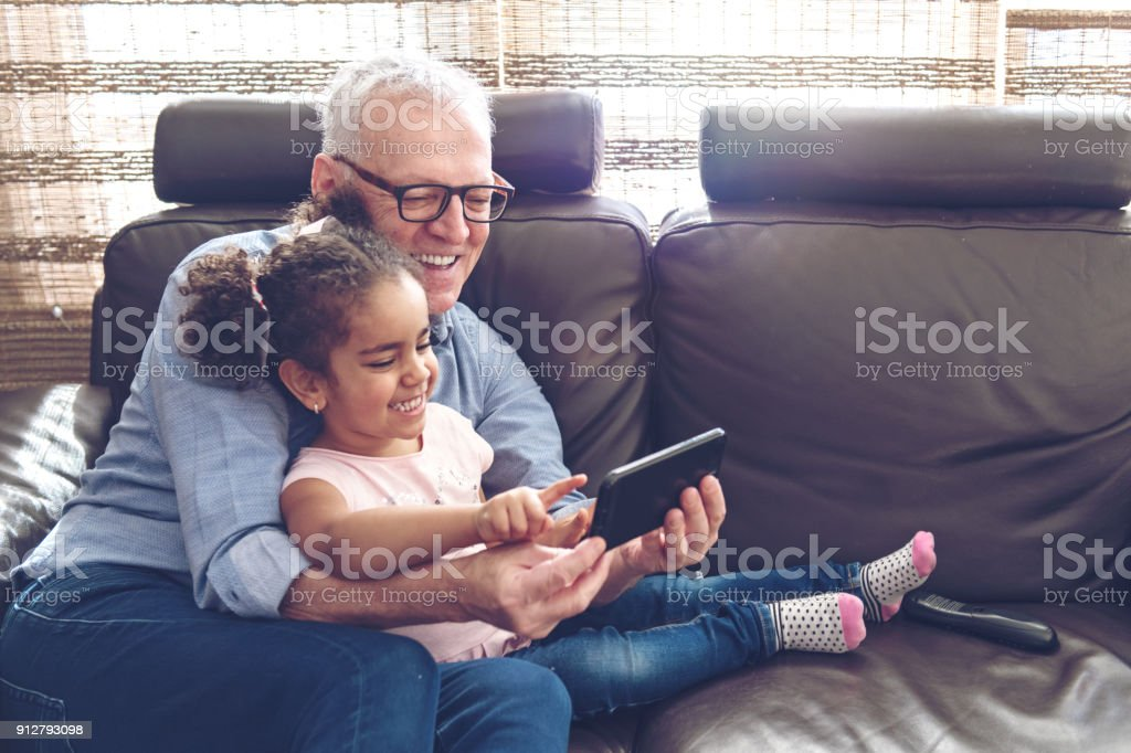 Grandfather playing with granddaughter on a mobile stock photo