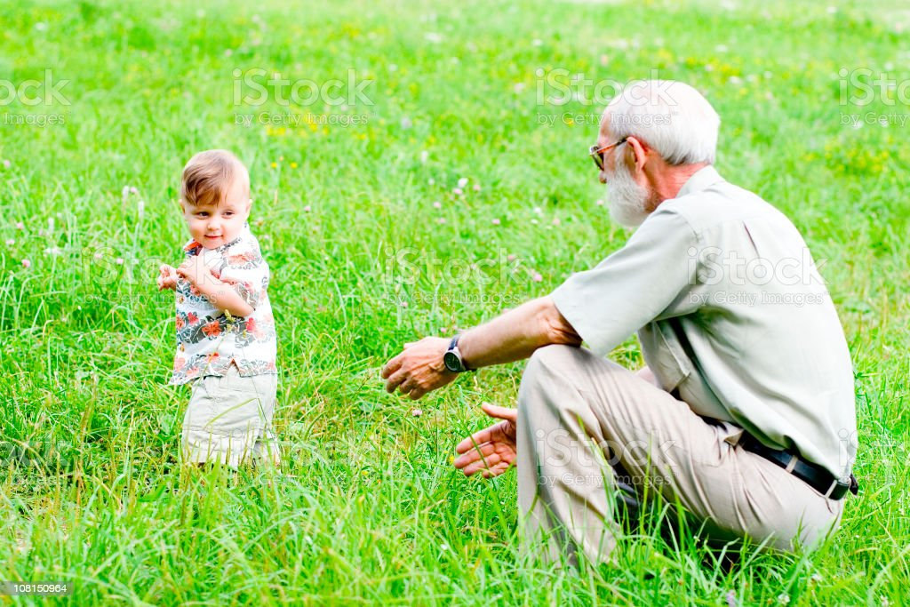 Grandfather Playing with Toddler Outside in Park royalty-free stock photo