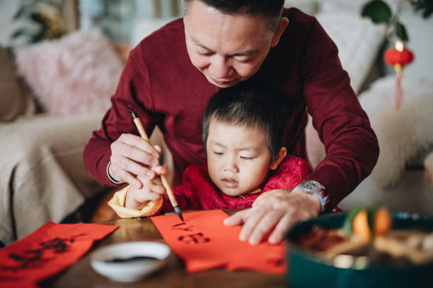 Grandfather practising Chinese calligraphy for Chinese New Year Fai Chun (Auspicious Messages) and teaching his grandson by writing it on a piece of red paper