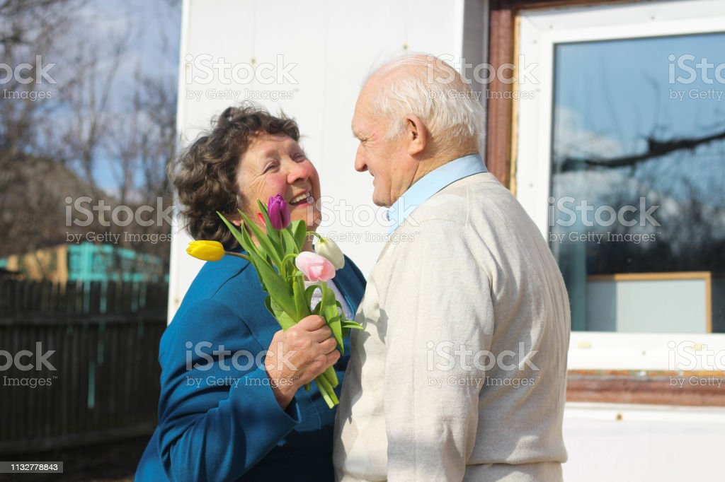 grandfather presenting flowers grandmother outside