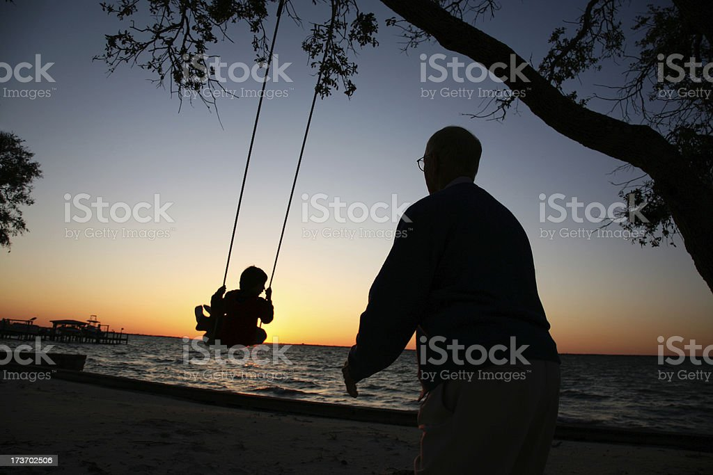 Grandfather pushes Grandson on swing set playing at sunset  silhouette royalty-free stock photo
