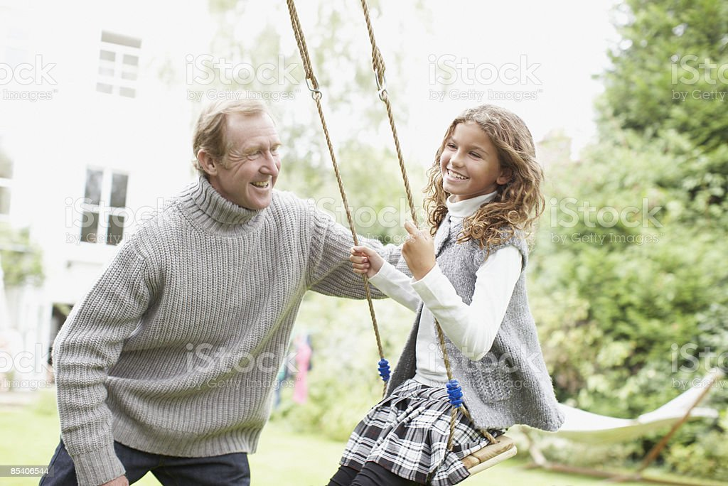 Grandfather pushing granddaughter on swing royalty-free stock photo