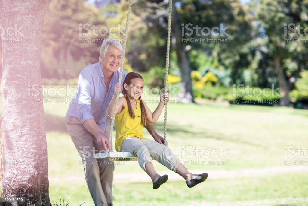 Grandfather pushing his granddaughter on swing stock photo