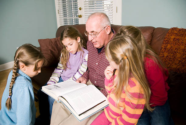 Grandfather Reading a book to grandchildren Little girls listening to a story.More in this series can be found here: illiteracy stock pictures, royalty-free photos & images