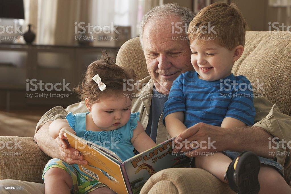 Grandfather reading book to grandchildren stock photo