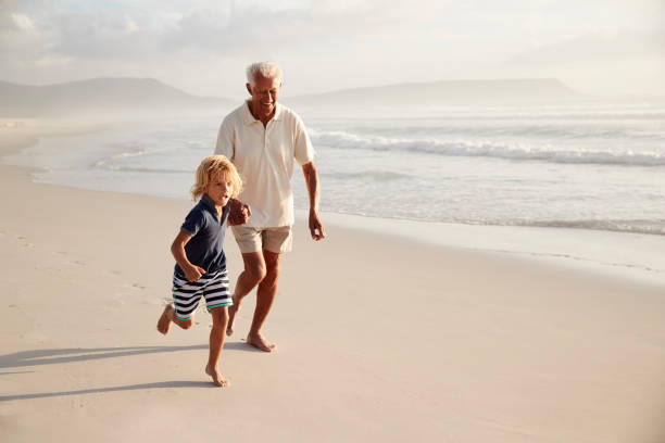 Grandfather Running Along Beach With Grandson On Summer Vacation Grandfather Running Along Beach With Grandson On Summer Vacation grandson stock pictures, royalty-free photos & images