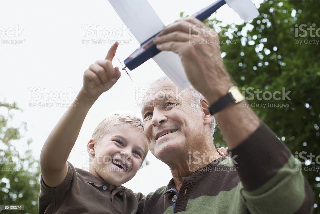 Grand-père montrant son petit-fils Jouet avion photo libre de droits