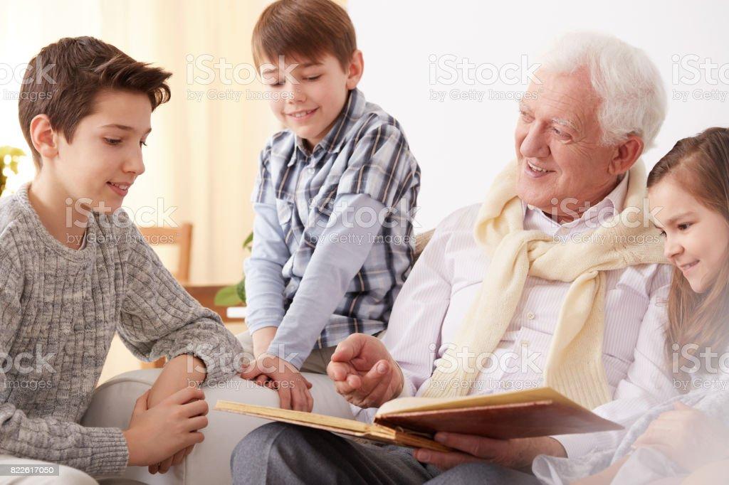 Grandfather showing photos to grandchildren - foto stock