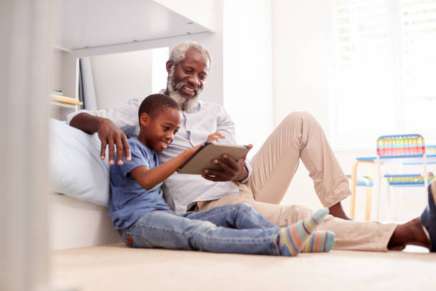 Grandfather Sitting With Grandson In Childs Bedroom Using Digital Tablet Together Grandfather Sitting With Grandson In Childs Bedroom Using Digital Tablet Together grandson stock pictures, royalty-free photos & images