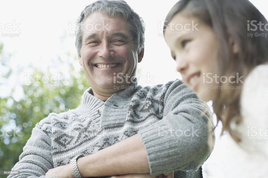 Grandfather smiling at granddaughter royalty-free stock photo