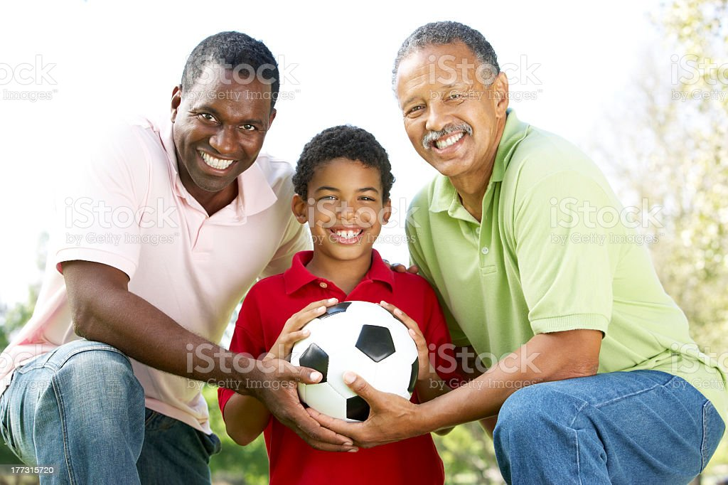 Grandfather son and grandson holding soccer ball in Park royalty-free stock photo