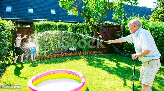 Grandfather uses a garden hose to spray water on his grandkids during a big water fight in a back yard. It is summer and the sun shines.