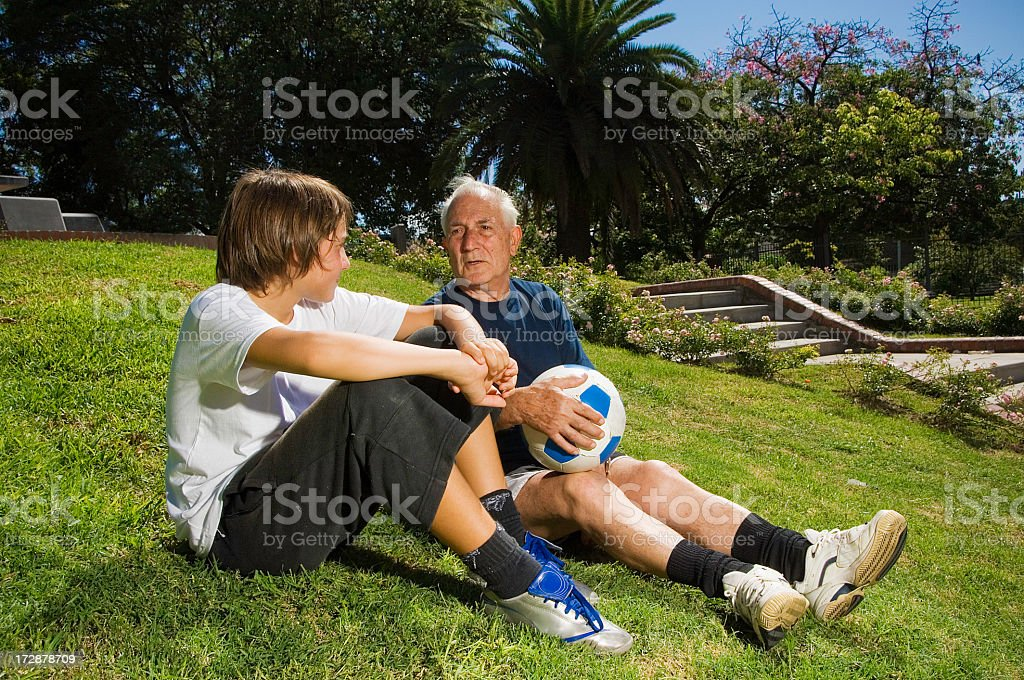 Grandfather talking with his Grandson in the park stock photo