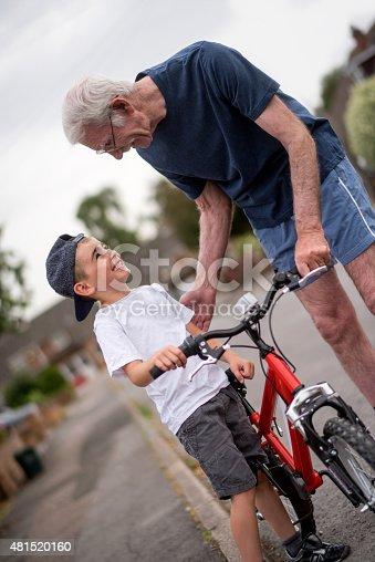 853720192 istock photo Grandfather teaching boy how to ride a bike 481520160