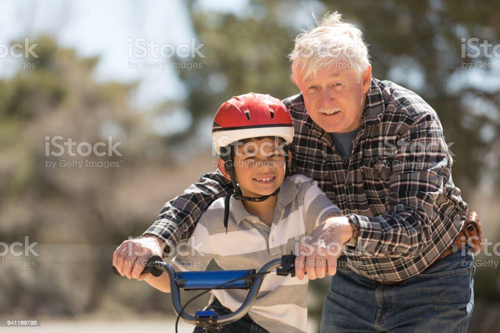 Grandfather Teaching Grandson Bicycle Riding stock photo
