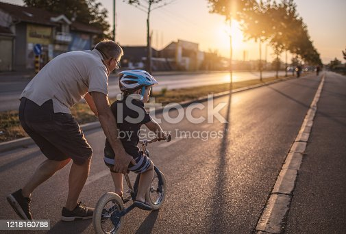 Grandfather teaching grandson biking outdoors