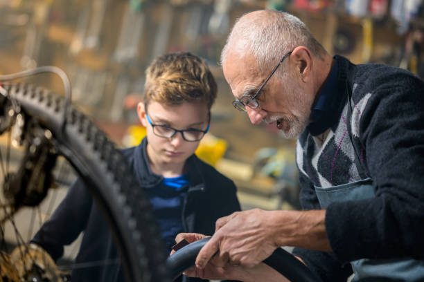 Grandfather teaching grandson how to patch a bicycle tire