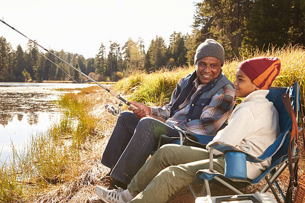 Grandfather Teaching Grandson To Fish By Lake stock photo