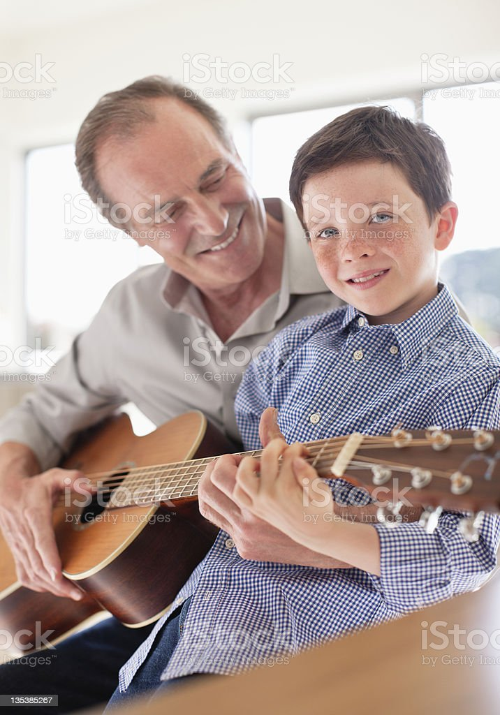 Grandfather teaching grandson to play guitar royalty-free stock photo