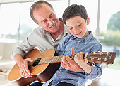 istock Grandfather teaching grandson to play the guitar 135385282