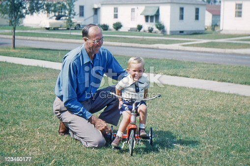 Grandfather helping grandson learn to ride tricycle. Iowa, USA 1953. Kodachrome scanned film with grain.