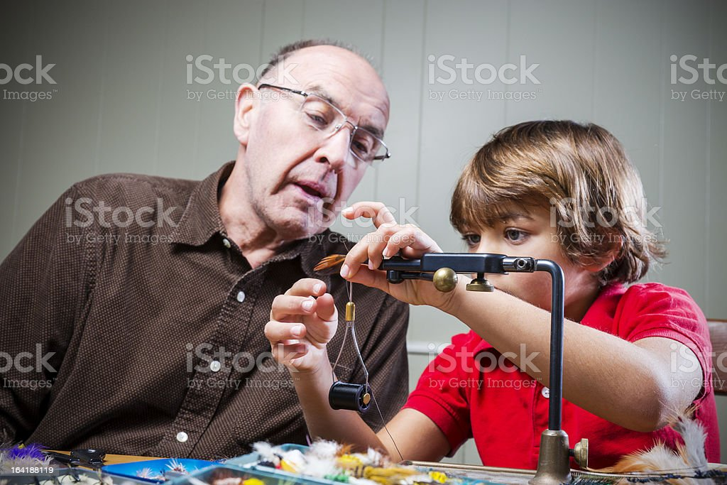 Grandfather teaching his grandchild how to tie fly-fishing flies royalty-free stock photo