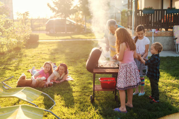 Grandfather teaching his grandchildren how to grill meal. Family gathering in backyard concept. Grandfather teaching his grandchildren how to grill meal. Family gathering in backyard concept. family bbq stock pictures, royalty-free photos & images
