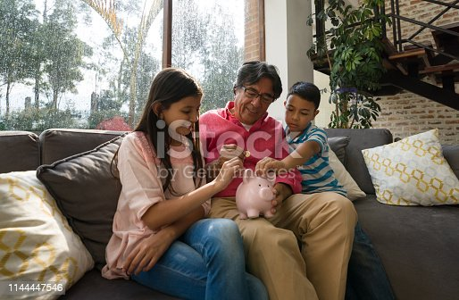 Grandfather teaching his grandkids to save money in piggy bank while sitting on couch at home all smiling