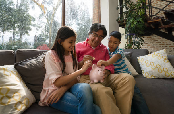 Grandfather teaching his grandkids to save money in piggy bank while sitting on couch at home Grandfather teaching his grandkids to save money in piggy bank while sitting on couch at home all smiling allowance stock pictures, royalty-free photos & images