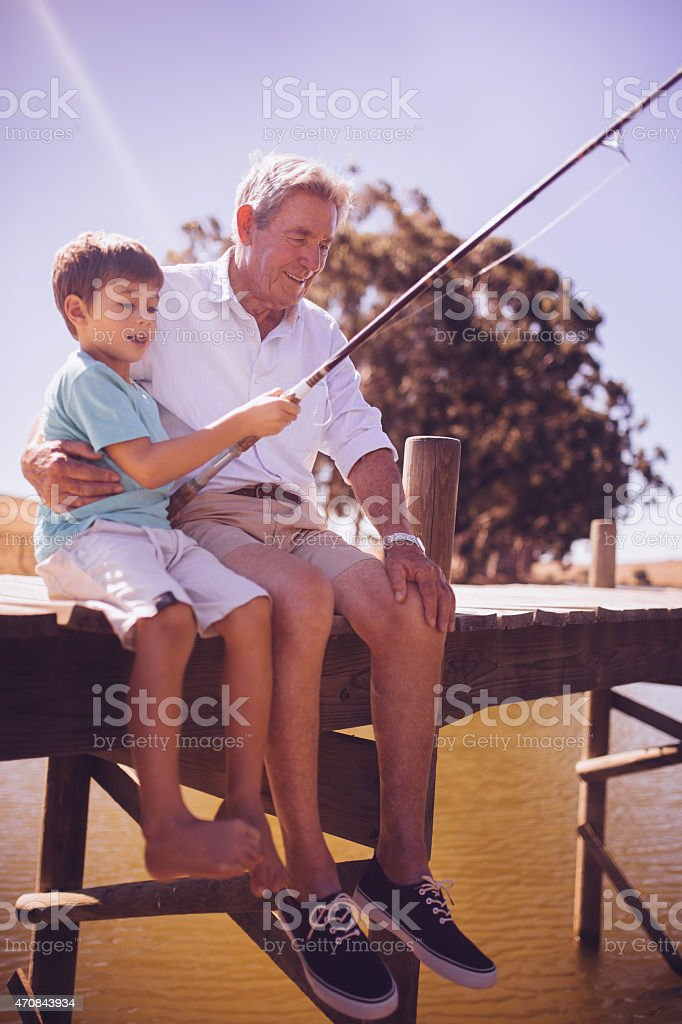 Grandfather teaching his grandson to fish at a lake stock photo
