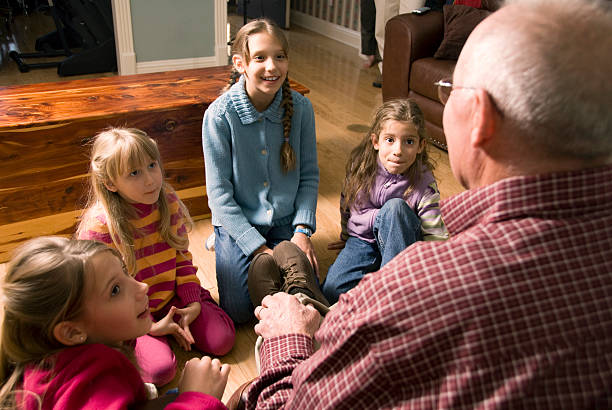 grandfather telling a story to grandchildren - fairy tale stock pictures, royalty-free photos & images