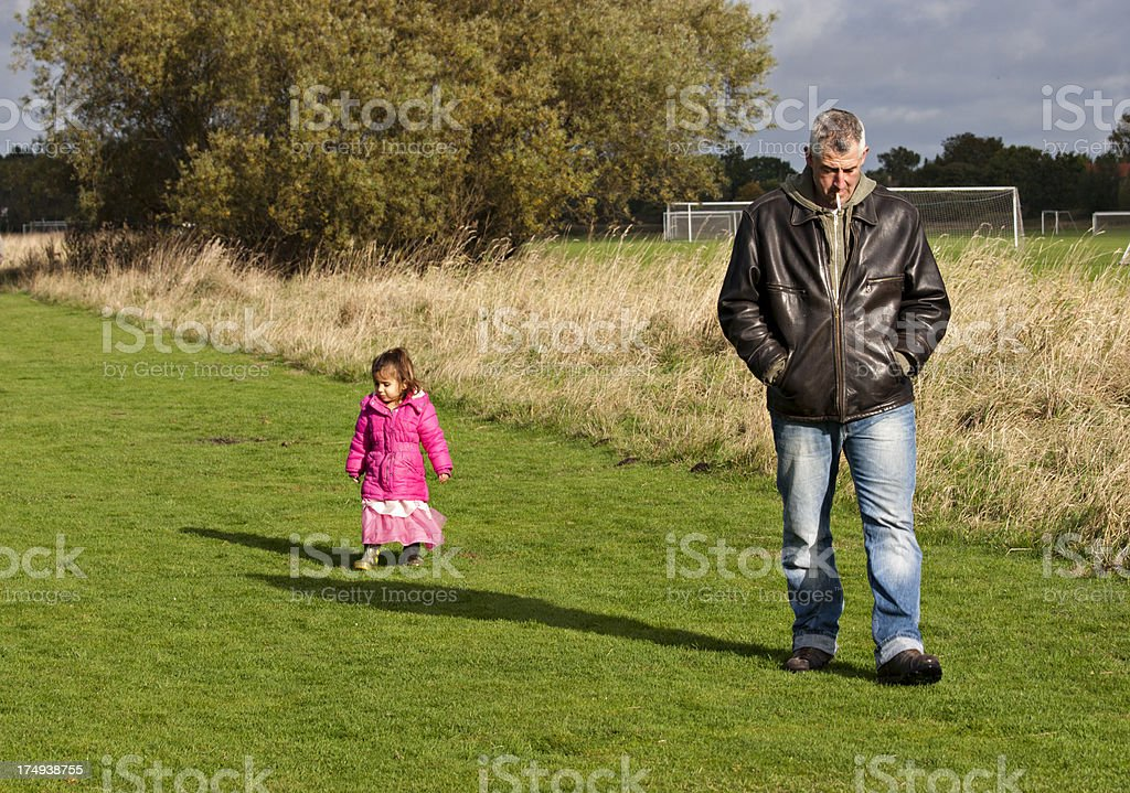 grandfather walking in the park with granddaughter royalty-free stock photo