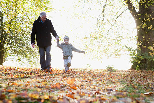 Grandfather walking outdoors with grandson in autumn stock photo