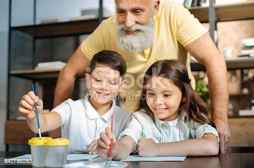 istock Grandfather watching grandchildren washing brush and choosing color 842785252