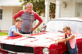 Grandfather With Grandchildren Cleaning Restored Classic Car Smiling To Camera