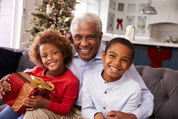Grandfather With Grandchildren Opening Christmas Gifts stock photo