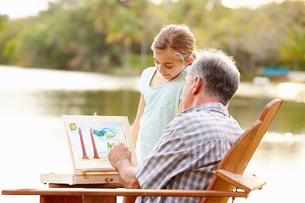 großvater und enkelin malerei landschaft im freien - senior bilder wasser stock-fotos und bilder