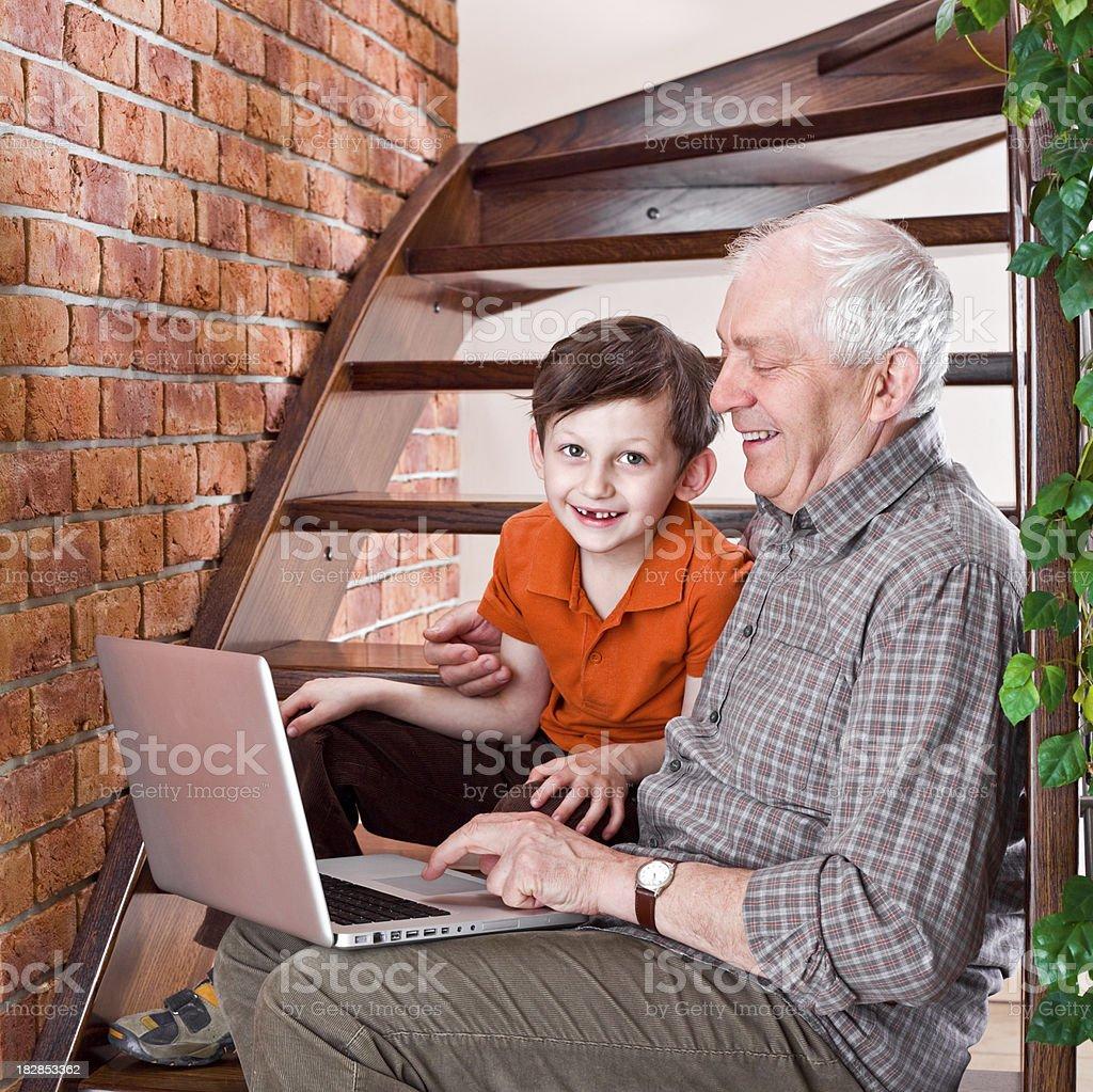 Grandfather with grandson enjoying laptop royalty-free stock photo