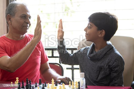 Grandfather with grandson giving high five and celebrating while playing chess at home