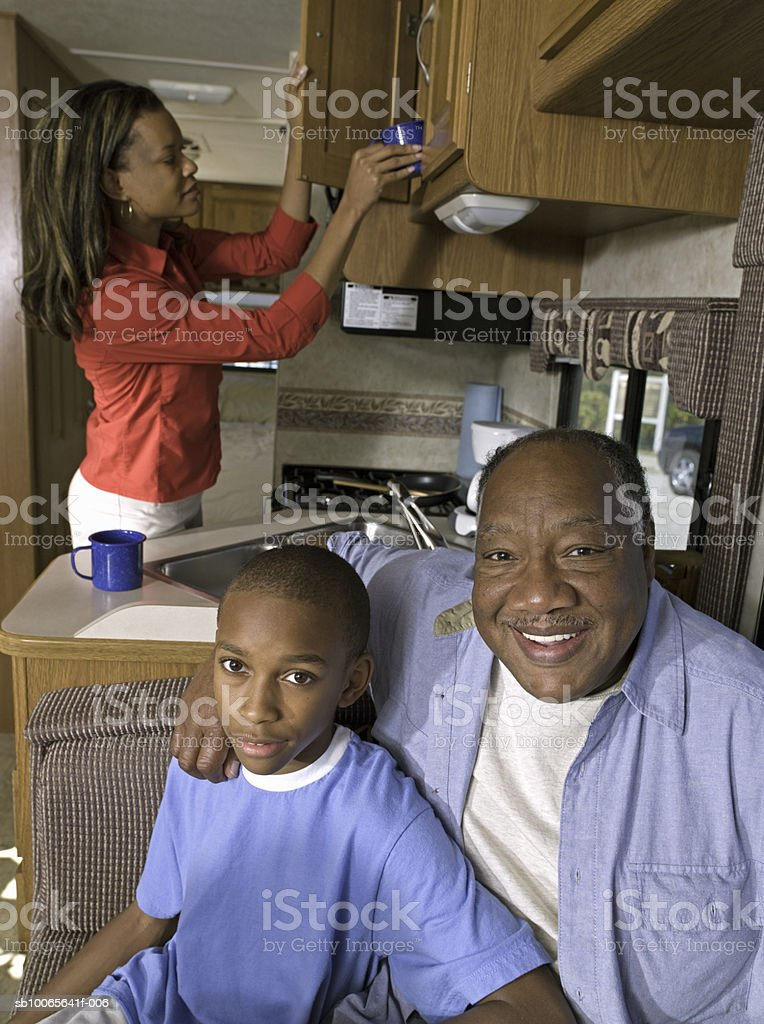 Grandfather with grandson (12-13) mother cooking in background in motorhome foto stock royalty-free