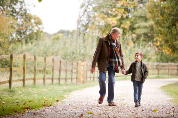 Grandfather With Grandson On Autumn Walk In Countryside Together Grandfather With Grandson On Autumn Walk In Countryside Together grandson stock pictures, royalty-free photos & images
