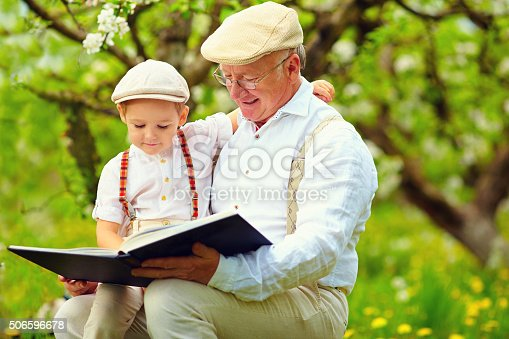 istock grandfather with grandson reading book in spring garden 506596678