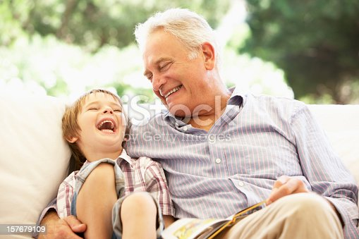istock Grandfather With Grandson Reading Together On Sofa 157679109
