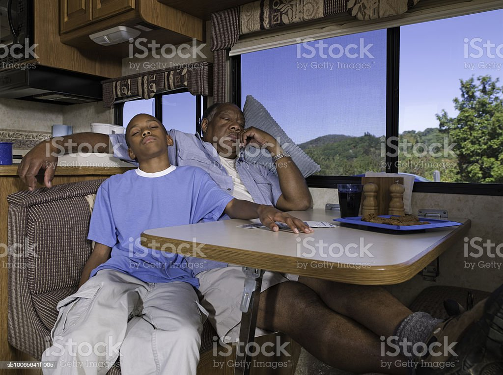 Grandfather with grandson (12-13) sleeping at kitchen table foto de stock royalty-free