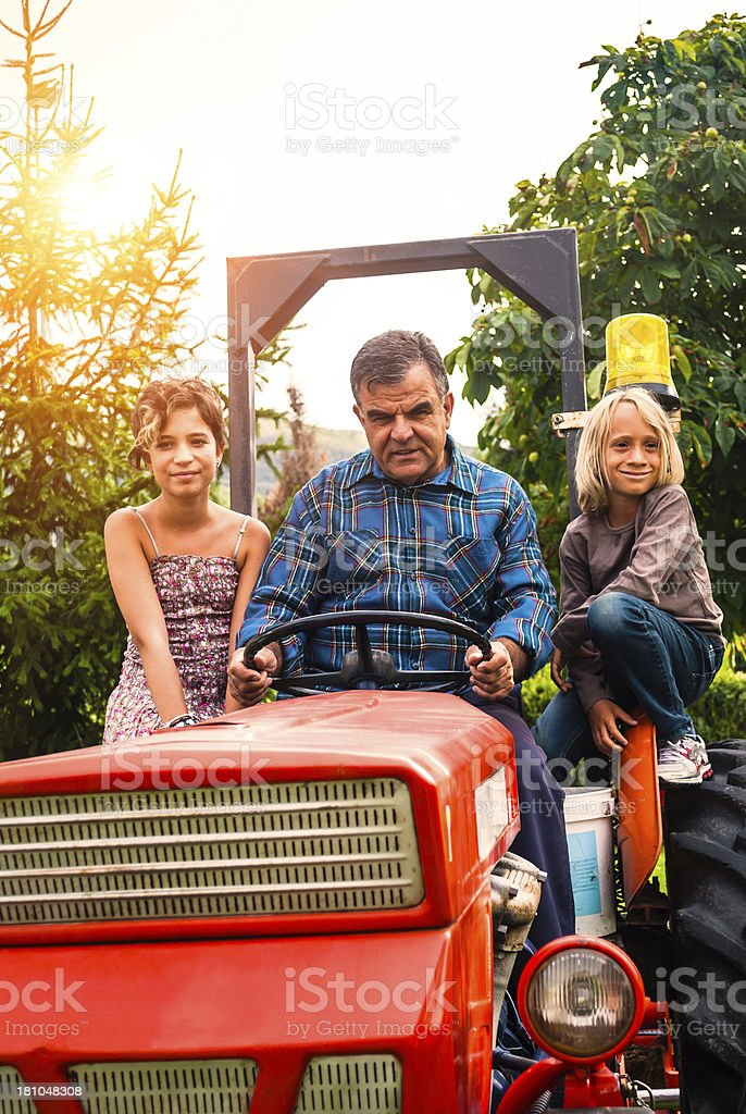 Grandfather with his children on the tractor stock photo
