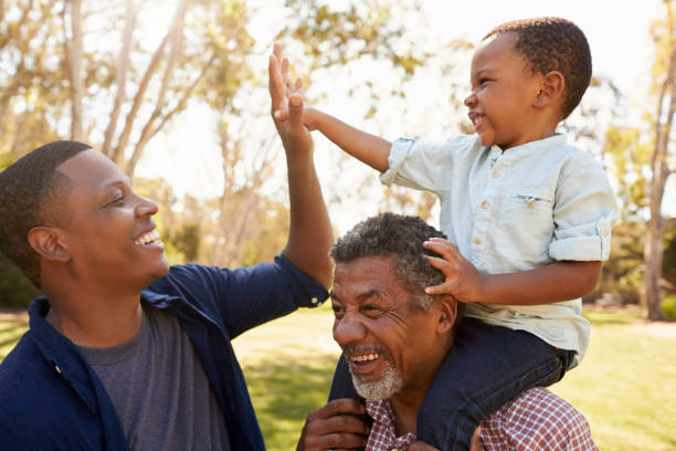Grandfather With Son And Grandson Having Fun In Park stock photo
