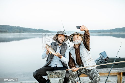 992209122istockphoto Grandfather with son fishing on the lake 1157290074