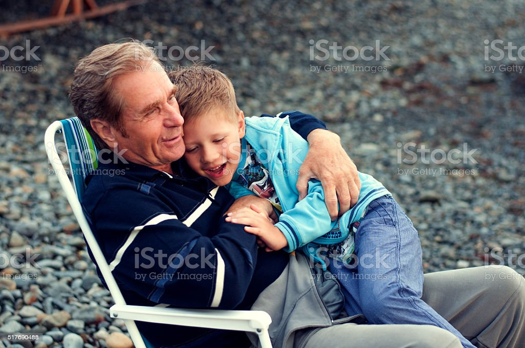 grandfather with the grandson on the beach stock photo