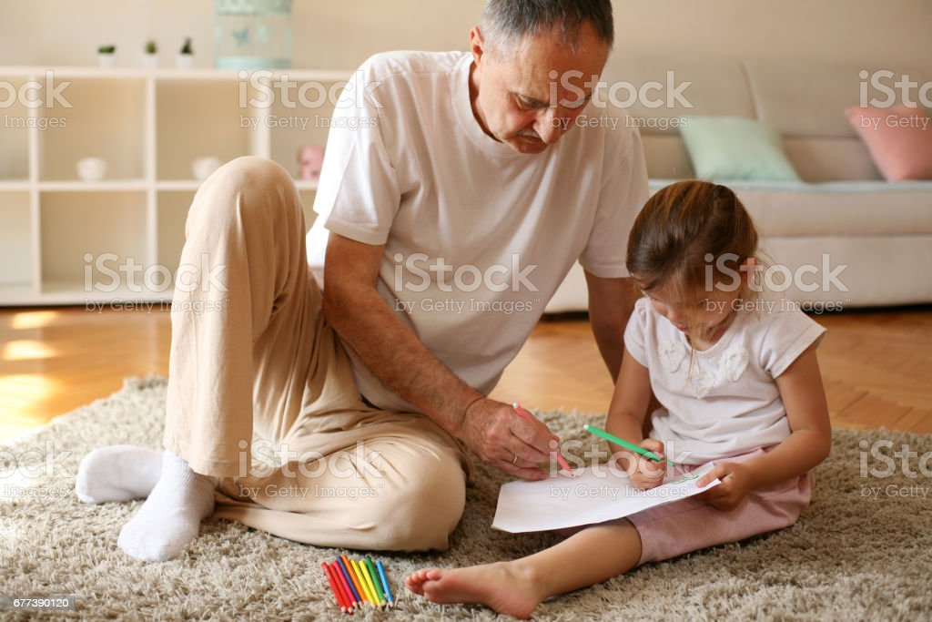 Grandfather working homework with granddaughter. stock photo