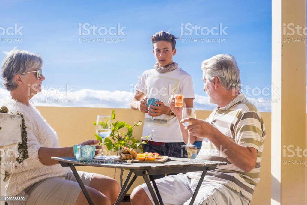 grandfathers adult mature and teenager nephew enjoy outdoor in the terrace some leisure with food and drinks. ocean and city view, vacation sunny day nice weather concept and background. happy people family together stock photo